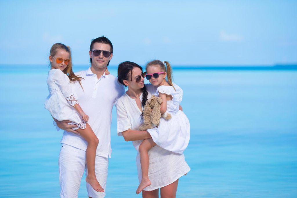 famiglia vestita di bianco con occhiali sole al mare